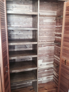 The finished linen closet with lots of shelving and rods to hang blankets